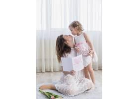 年轻的母女俩手持贺卡在家中接吻_4048467