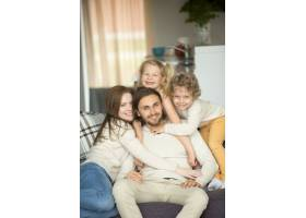 幸福的家庭孩子们坐在沙发上看相机肖像_3938146