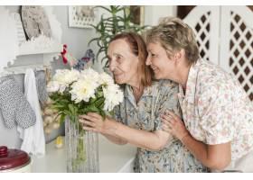 年长的母亲和成熟的女儿在家里闻着花瓶里的_5044016