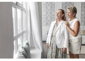 年长的母女在家中透过窗户看_5043975