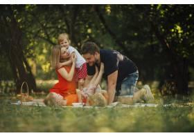 幸福的一家人在野餐毯子上玩耍_4961110