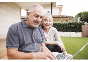 一对高年级夫妇在花园里使用笔记本电脑_3837393