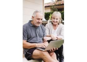 一对高年级夫妇在花园里使用笔记本电脑_3837396