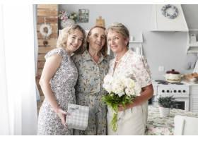三代妇女手持鲜花和礼物站在一起看着相机_5069814