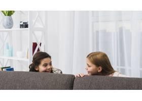 两个女孩在家里躲在沙发后面互相看着的特写_4105295