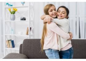 两个微笑的女孩在家中拥抱的特写_4105311