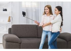 两个微笑的女孩站在沙发前用智能手机自拍_4105407