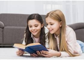 两个漂亮的女孩在家躺在地毯上一起看书_4124079