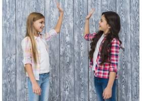 两个面带微笑的女孩站在灰色的木墙上击掌_4112521