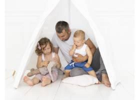 全景拍摄的父亲和他的孩子在帐篷里玩耍_5179771
