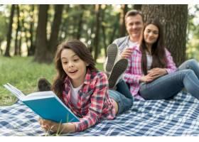 公园里一对夫妇坐在他们可爱的女孩身后_4958780