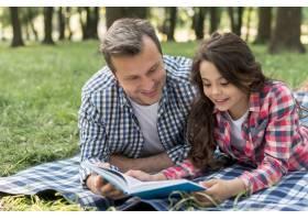 公园里微笑的父女躺在毯子上看书的特写_4975833