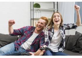 兴奋的年轻夫妇在家里玩电子游戏时欢呼_3882657