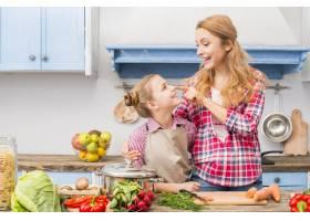 厨房里微笑的年轻母亲用手指摸着女儿的鼻子_4400041