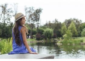 可爱的女孩从后面坐在湖边_4962277