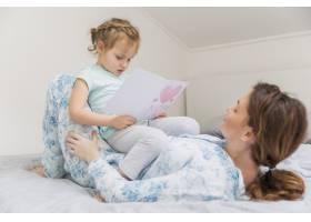 可爱的小女孩坐在家里坐在妈妈的肚子上看贺_4040580