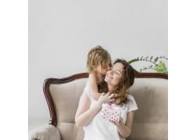 可爱的小女孩拿着坐在沙发上的礼品盒亲吻她_4048327