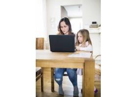 一个女孩在木桌上用笔记本电脑看着她的母亲_2602090
