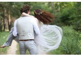一个男人怀里抱着一个女孩在树林里转来转_2462172