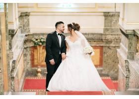 一个穿着黑色西装的漂亮年轻人和他的新娘站_2528623