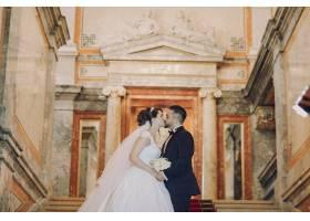 一个穿着黑色西装的漂亮年轻人和他的新娘站_2528625