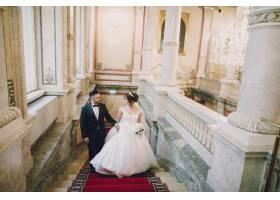 一个穿着黑色西装的漂亮年轻人和他的新娘站_2528626