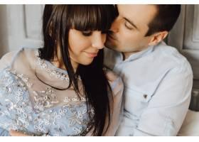 美丽的年轻夫妇坐在床上拥抱温柔_3339459