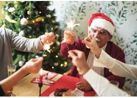 老人与家人在节日餐桌上手持孟加拉火_3334078