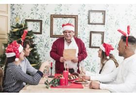 老人拿着纸站在节日餐桌旁_3329685