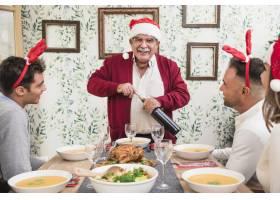 节日餐桌上戴着圣诞帽的老人打开酒瓶_3319386