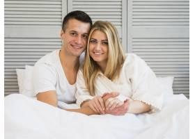英俊开朗的男子在床上拥抱年轻女子_3544806