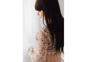 身穿米色长裙的美丽孕妇站在明亮舒适的房间_3339460