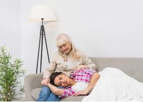 面带微笑的小女儿坐在沙发上睡在年长母亲的_3764569