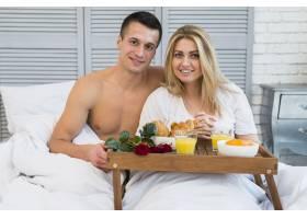 飞机上微笑的夫妇在床上吃早餐_3524264