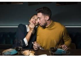 餐厅里一名男子嘴里叼着叉子旁边坐着一_3597242