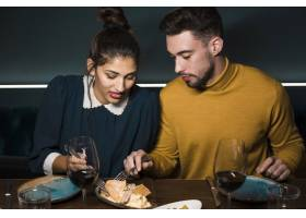 餐厅里年轻的男女拿着叉子坐在餐桌旁端_3607921