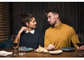 餐厅里年轻的男女端着酒杯和食物坐在餐桌旁_3597245