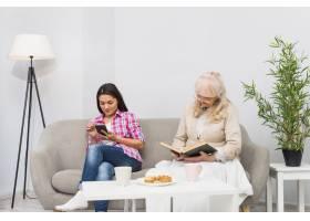 高龄母亲坐在女儿身边用手机看书早餐摆在_3764615