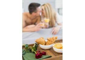 早餐桌上的食物和鲜花靠近床上戴着眼镜的女_3553454