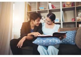 欢快的幸福夫妇在家里的沙发上放松_3398371