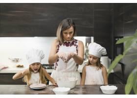 母亲和女儿在厨房里搅拌可可粉做饼干_3764550