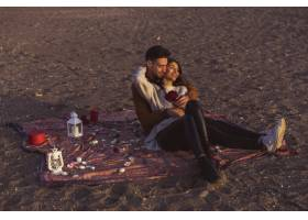 海边年轻夫妇在床单上拥抱_3631921