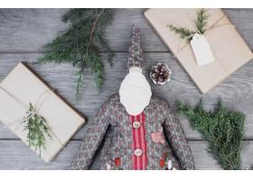 玩具圣诞老人在礼品盒和小树枝之间穿着外_3513803