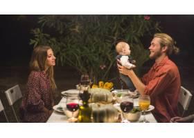 父亲在家庭晚餐上抱着小婴儿靠近女士_3212522