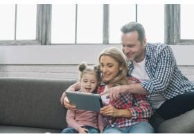 父亲在家里指着数字平板电脑妻子和女儿面_3808449