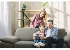 父母和女儿在家中客厅的沙发上使用数字平板_3808499