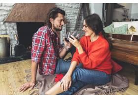 年轻夫妇在地板上喝酒_3607781