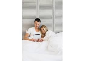 年轻夫妇在床上用毯子盖着平板电脑_3544770