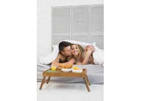 年轻男子在床上用毯子亲吻快乐的女子靠近_3553437