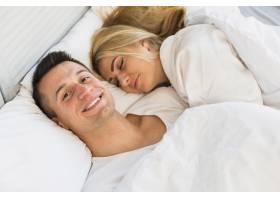 年轻男子微笑着靠近睡着的女人躺在床上的毯_3524209